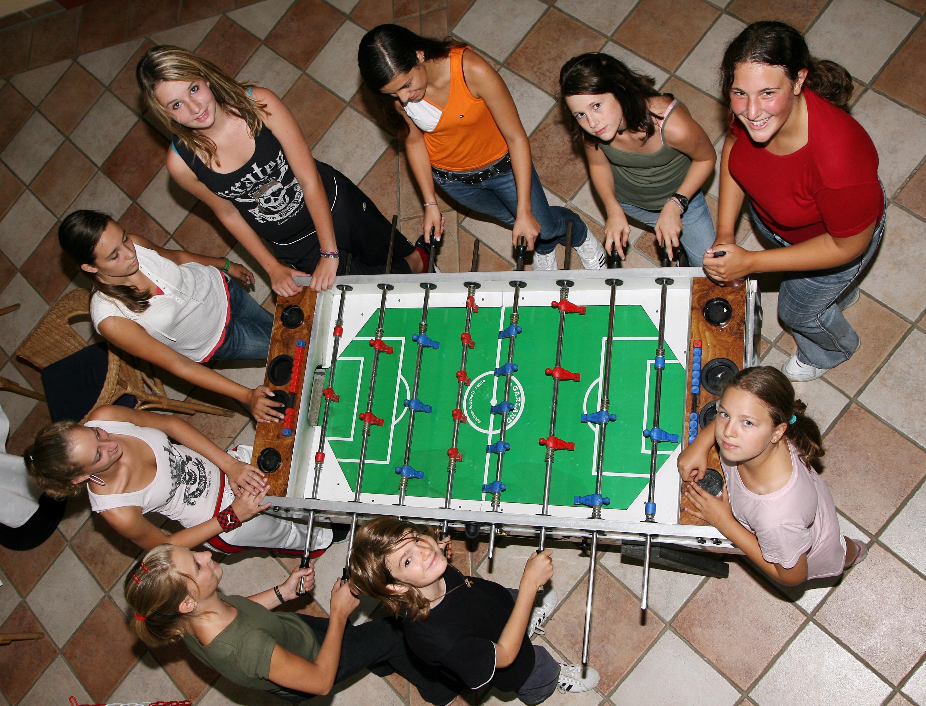 Eine Gruppe von Teens spielt gemeinsam Tischfußball. JUFA Hotels bietet erlebnisreiche Feriencamps in den Bereichen Sport, Gesundheit, Bildung und Sprachen.