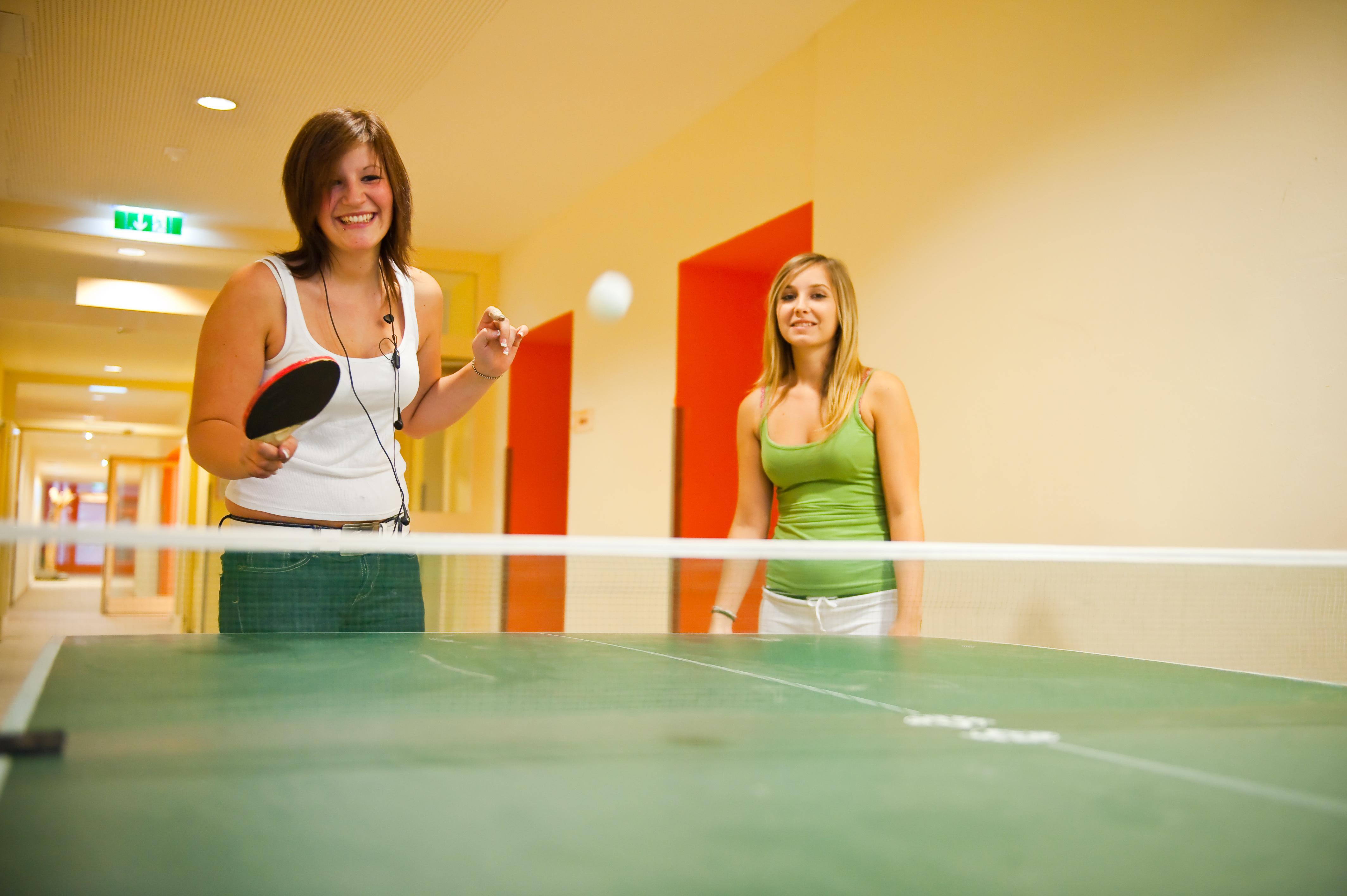 Sie sehen zwei Mädchen beim Tischtennis spielen und eine Tischtennisplatte. Der Ort für erholsamen Familienurlaub und einen unvergesslichen Winter- und Wanderurlaub.